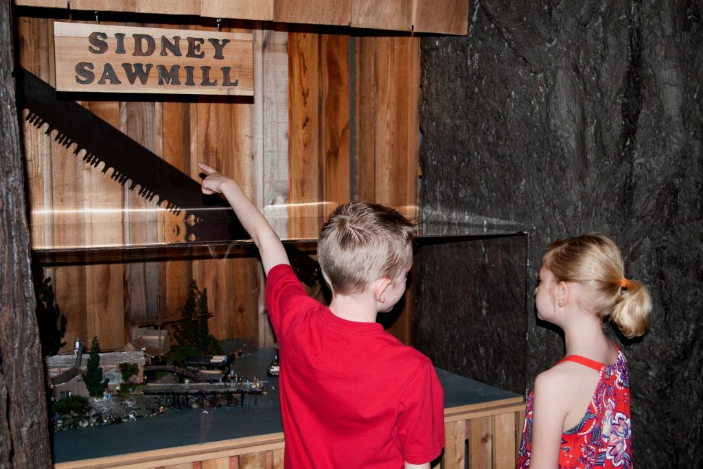Child pointing at Sidney Sawmill display