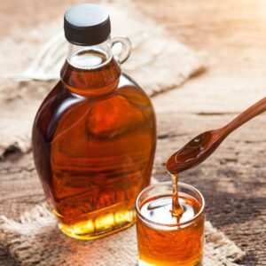 A clear bottle of maple syrup. There is a small glass in front of the bottle full of syrup with a wooden spoon lifting syrup out of it.