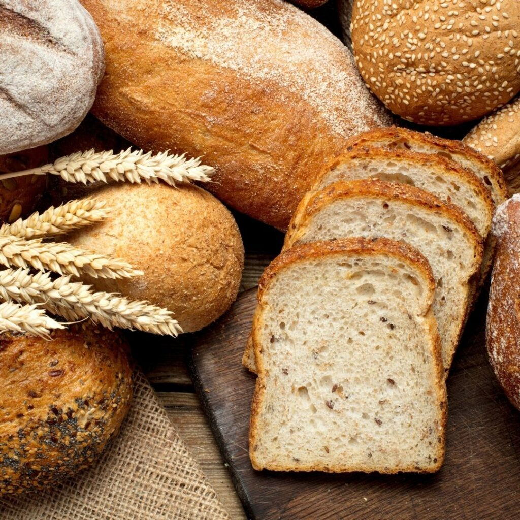 A close up photo of loaves and sliced bread on a wooden background.