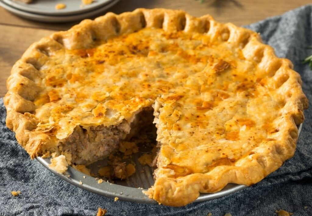 A tourtiere in a metal dish. The upper pastry is a golden brown and the edge is crimped. There is a piece missing.